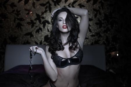 young sex: Сексуальная женщина позирует с наручниками в постели, бдсм