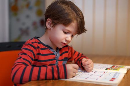 matematica: El niño pequeño escribir ejercicio de matemáticas en casa