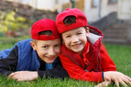 Little boys laughing in grass at backyard photo
