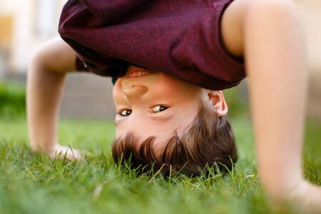 headstand: Little boy headstand in grass and laughing, outdoor portrait Stock Photo