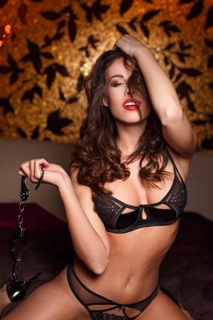 sexo pareja joven: Mujer atractiva con el con esposas en la cama, juguete del sexo