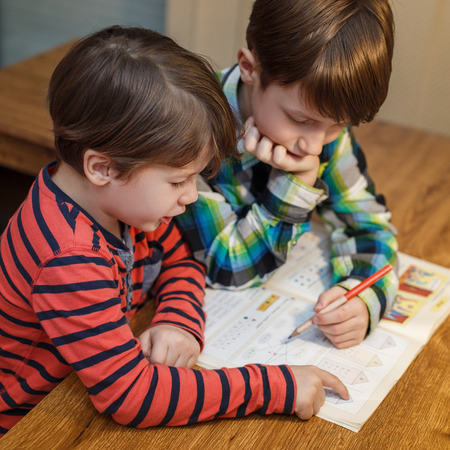 solving: Little genius boy help his brother with homework, problem solving, education Stock Photo