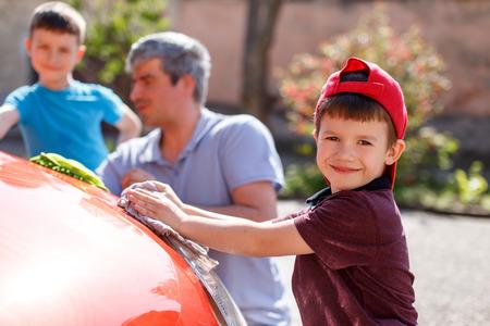 autolavaggio: Famiglia giorno lavaggio auto, piccolo ragazzo che pulisce i riflettori, il padre e il fratello in sfondo fuori fuoco
