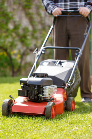 mowing grass: Senior man mowing grass with machine outdoor