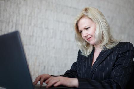 revenge: Trolling businesswoman typing on laptop in office Stock Photo