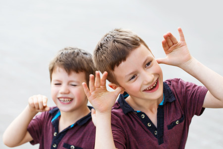 misbehavior: Little hyperactive caucasian brothers playing outdoor