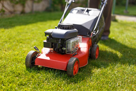 Pensioner mowing lawn with machine outdoor Stockfoto