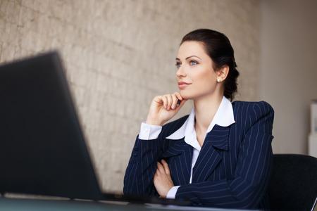 Confident brunette businesswoman sitting at desk in office