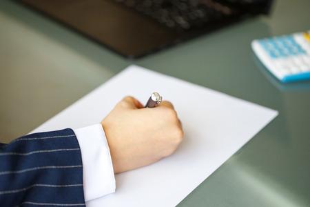 hand wear: Businesswoman hand in formal wear write on blank paper closeup