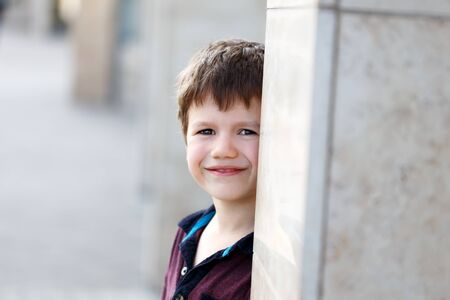 seek: Little boy hide and seek behind pillar outdoor portrait