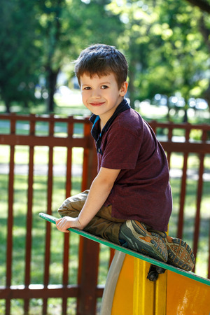 jungle gym: Little boy climbing on the top of jungle gym outdoor portrait