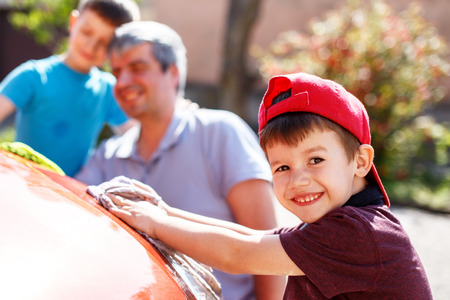 Family car wash, little boy cleaning spotlight, father and brother in background Stock Photo