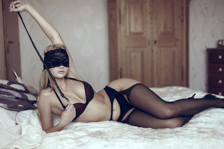 mujeres eroticas: Mujer atractiva en la cubierta del ojo de encaje con el l�tigo en la cama, bdsm