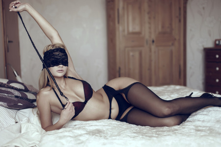 hot sex: Sexy woman in lace eye cover with whip on bed, bdsm Stock Photo