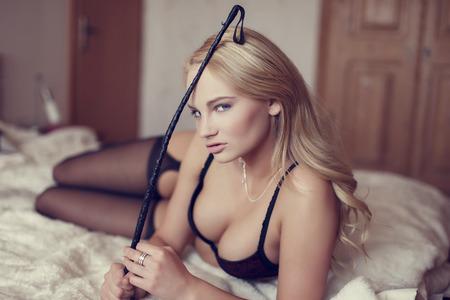 sex: Sexy blonde vrouw met zweep op bed, bdsm