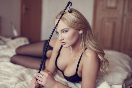 romance sex: Sexy blonde woman holding whip on bed, bdsm