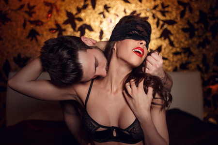 romance sex: Sexy woman in lace eye cover and red lips with young lover foreplay in hotel room Stock Photo