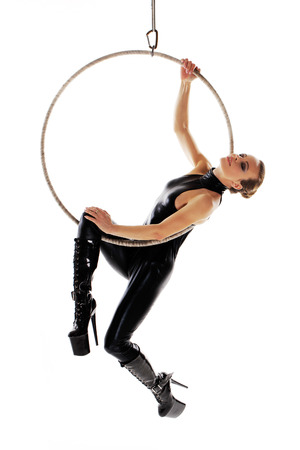 catsuit: Sexy woman performer in latex catsuit on aerial hoop isolated on white
