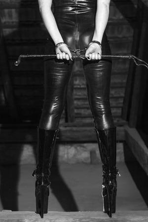 femme sexe: Corps de la femme sexy en combinaison de latex dominatrice tenant fouet en noir de grange et BDSM blanc