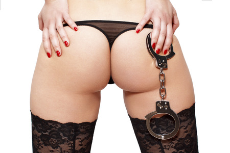 nude ass: Woman holding handcuffs on ass closeup isolated on white bdsm