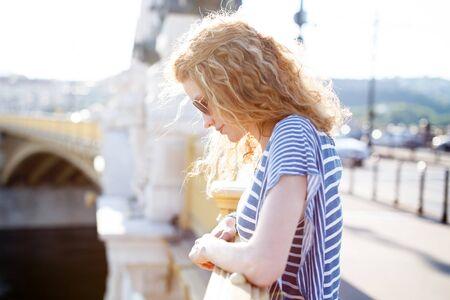 cabello rizado: Mujer con el pelo rizado que mira hacia abajo en el puente en la puesta del sol