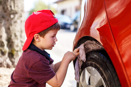 clean car: Little boy in red cap cleaning wheel Stock Photo