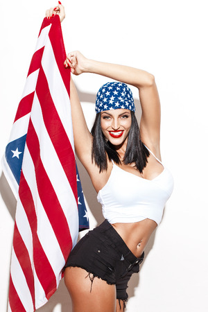 julio: Mujer atractiva que sostiene la bandera de EE.UU. en pañuelo en blanco cuarta pared del día de la independencia julio