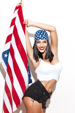femme brune sexy: Sexy femme tenant le drapeau usa en foulard au mur blanc quatri�me de juillet ind�pendance jour