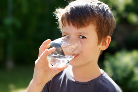 glass of water: Little caucasian boy drink water in nature