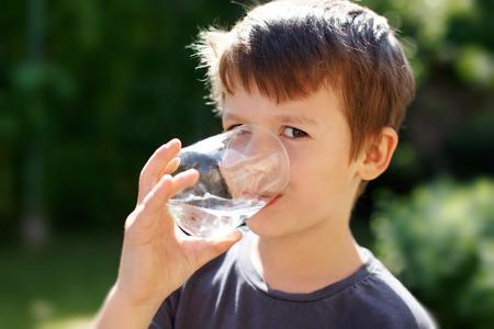vasos de agua: Poco caucásica beber agua chico en la naturaleza Foto de archivo
