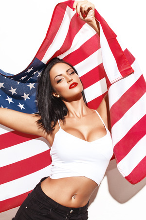donna sexy: Donna sexy che tiene bandiera USA a muro bianco Fouth di luglio Archivio Fotografico