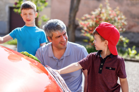 dad son: Father teaching son cleaning the spotlight family car wash Stock Photo