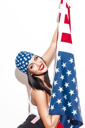 independencia: Mujer atractiva con EE.UU. bandera que presenta en la pared blanca