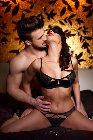 men sex: Sexy couple kissing on bed at night foreplay bdsm Stock Photo