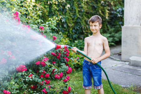 sprinkler: Little boy watering in garden on hot summer day
