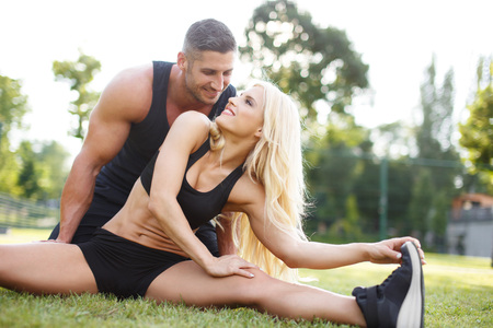 outdoor fitness: Young couple doing exercise outdoor on grass. Blonde woman stretching with personal fitness trainer