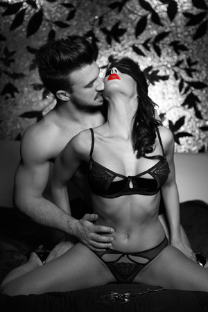 erotic women: Sexy couple kissing on bed at night foreplay bdsm. Selective black and white coloring with red lips