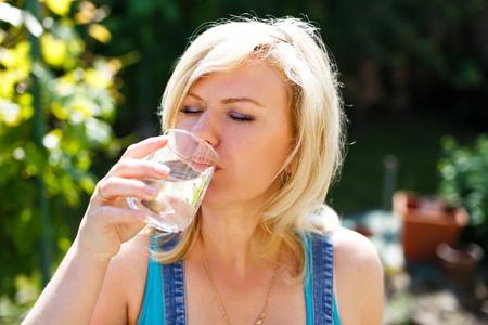 hot summer: Mujer rubia de agua potable en el caluroso d�a de verano, retrato al aire libre