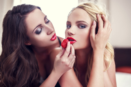 lesbian erotic: Sexy lesbian couple eating strawberry on bed Stock Photo