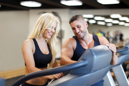 Personal trainer set difficulty on treadmill for blonde woman in gym