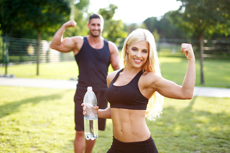 Fit couple in nature with bottle of water, blonde woman showing biceps, healthy lifestyle