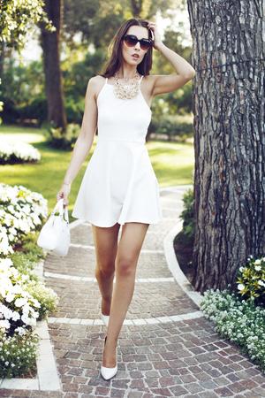 urban fashion: Rich fashionable brunette woman walking in park