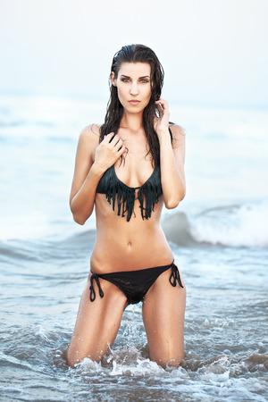 mujer arrodillada: Mujer morena sexy bikini de rodillas en el agua Foto de archivo