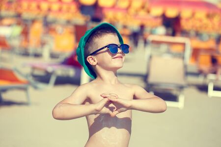 sea beach: Happy little boy enjoying the summer holiday, showing heart, vintage style, outdoor