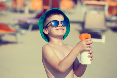 Little boy applying sunscreen spray, vintage style Stock Photo