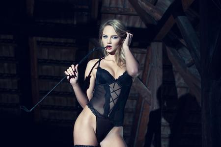 Sexy blonde woman in underwear bite whip at barn, bdsm 스톡 콘텐츠