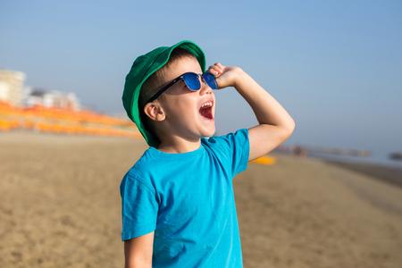 hurray: Little boy enjoying summer and shouting on beach