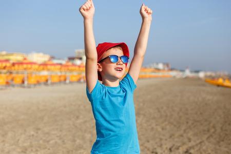 hurray: Little boy enjoying summer holiday, hands up