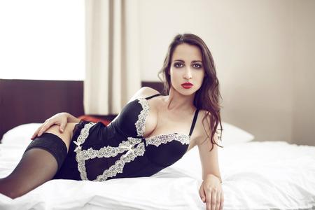 tetas: Mujer morena sexy con tetas grandes en la ropa interior que pone en cama Foto de archivo