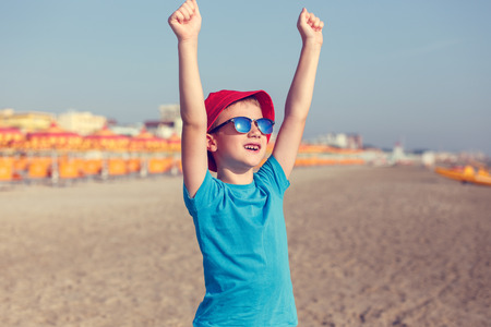 hurray: Little boy enjoying summer holiday, hands up, vintage style